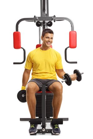 Young man exercising with weights on a fitness machine and smiling at the camera isolated on white background
