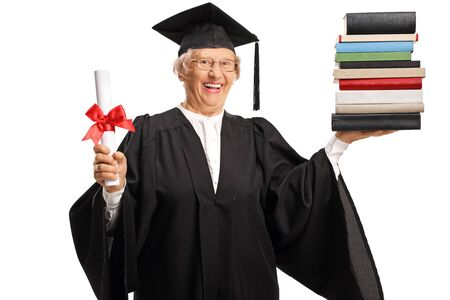 Senior woman in a graduation gown holding a diploma and a pile of books isolated on white background