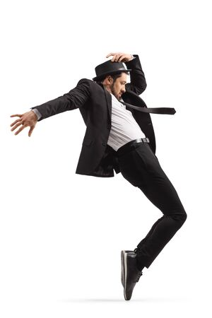 Full length profile shot of a male dancer in a black suit standing tiptoes and holding hat isolated on white background Stock Photo