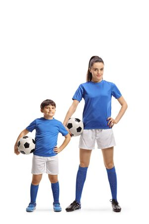 Full length portrait of a boy and young female in sports jersey holding soccer balls isolated on white background