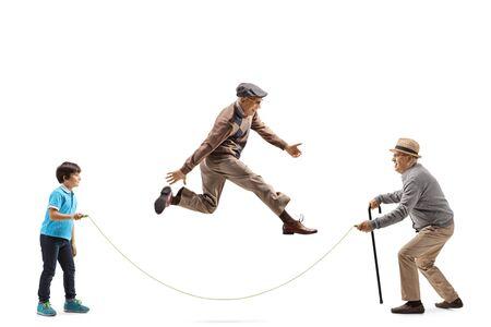 Profilaufnahme in voller Länge von einem Großvater und einem Enkel, die ein Seil halten, und einem älteren Mann, der isoliert auf weißem Hintergrund überspringt
