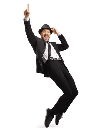 Full length portrait of a young smiling man in suit dancing on tiptoes isolated on white background
