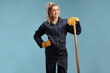 Female farmer in a uniform leaning on a working tool isolated over blue background
