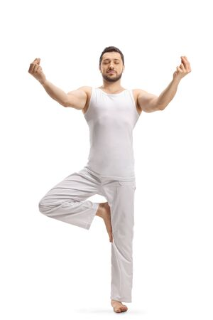 Full length portrait of a man in a standing position practicing a yoga pose isolated on white background
