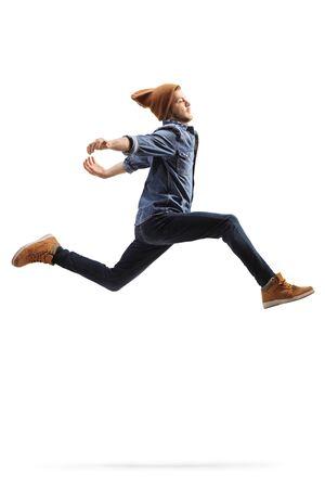 Kerel in jeans die een sprong uitvoert die op witte achtergrond wordt geïsoleerd