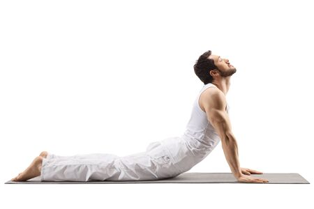Young muscular man stretching on a mat isolated on white background