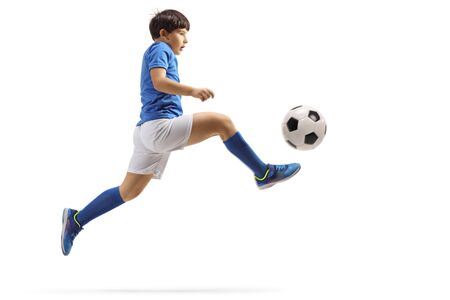 Full length profile shot of a boy jumping and kicking a soccer ball isolated on white background