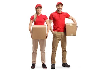 Full length portrait of a delivery male and female in uniforms holding packages isolated on white background