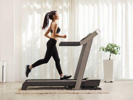 Pełne zdjęcie profilowe młodej kobiety biegającej na bieżni w pomieszczeniu