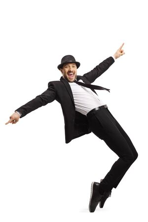 Full length shot of a smiling guy in a suit dancing and pointing with fingers isolated on white background