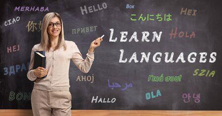 Profesor de inglés de pie frente a una pizarra con hola escrito en diferentes idiomas y apuntando con tiza a un texto aprender idiomas