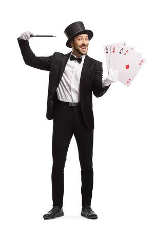 Retrato de cuerpo entero de un mago con una varita mágica y 4 ases de cartas aislado sobre fondo blanco. Foto de archivo