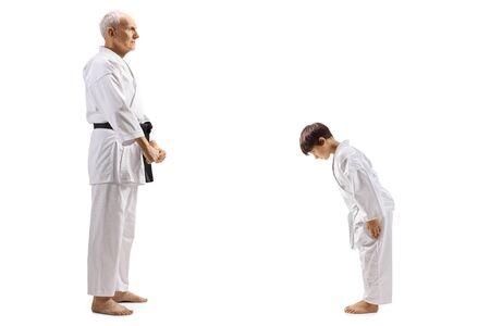 Colpo di profilo integrale di un ragazzo in kimono di karate che si inchina davanti al suo anziano istruttore di karate isolato su sfondo bianco