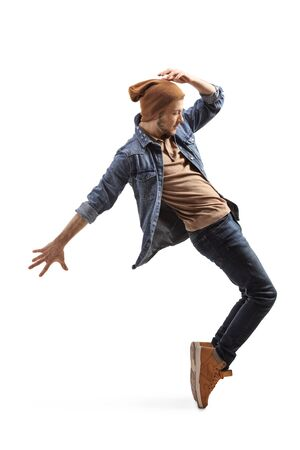 Full length profile shot of a young guy in jeans and woolen hat dancing on tiptoes isolated on a white background