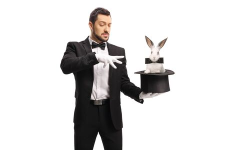 Young male magician making a magic trick with a rabbit in a top hat isolated on white background