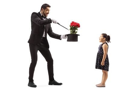 Full length shot of a magician making flowers appear from a hat and a surprised little girl watching isolated on white background Stock Photo