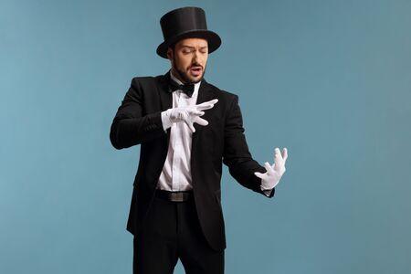 Mago macho realizando un truco con las manos aisladas sobre fondo azul.