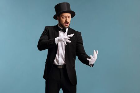 Male magician performing a trick with hands isolated on blue background