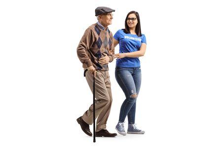 Aufnahme in voller Länge von einer jungen Freiwilligen, die einem älteren Mann mit einem Gehstock hilft, isoliert auf weißem Hintergrund