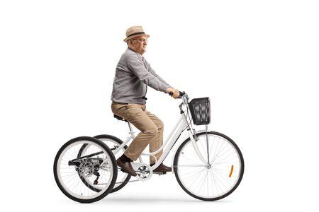 Älterer Mann, der ein weißes Dreirad fährt, das auf weißem Hintergrund lokalisiert wird