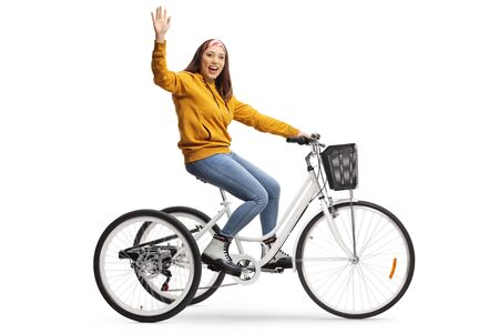 Cheerful young female riding a tricycle and waving at the camera isolated on white background