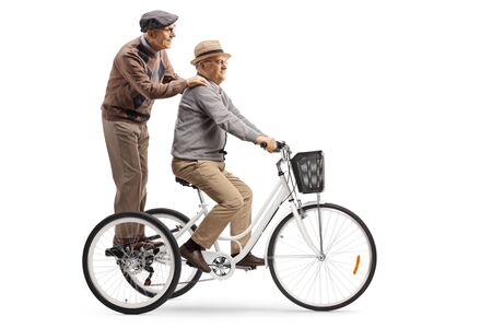 Elderly man riding a tricycle with another elderly man standing behind isolated on white background 스톡 콘텐츠