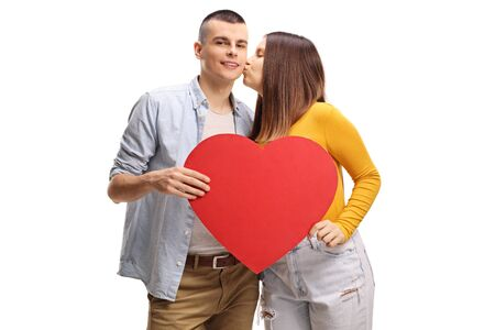 Young female kissing a guy holding a big red heart isolated on white background