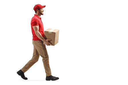 Full length profile shot of a delivery man carrying a package and walking isolated on white background