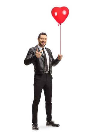 Full length portrait of a young trendy man holding a red heart balloon and pointing isolated on white background