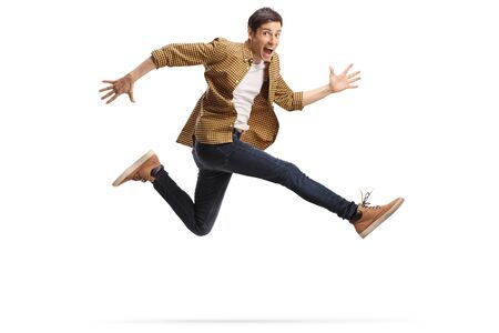 Casual happy young man jumping isolated on white background Foto de archivo
