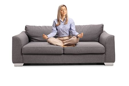 Young woman in formal clothes sitting on a sofa with crossed legs in a meditation pose isolated on white background Stock Photo