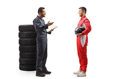Full length profile shot of an auto mechanic standing next to a pile of tires and talking to a car racer isolated on white background