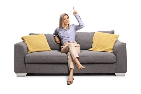 Blond woman sitting on a gray sofa and pointing above isolated on white background Foto de archivo