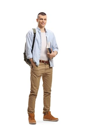Full length portrait of a male student with books and backpack and smiling at the camera isolated on white background