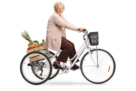 Happy senior woman riding a tricycle with a crate full of fruits and vegetables isolated on white background