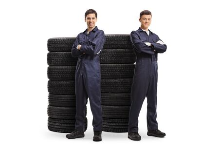 Full length portrait of young male auto mechanic workers posing with piles of tires isolated on white background