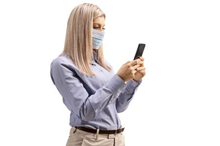 Woman wearing a medical mask and typing on a mobile phone isolated on white