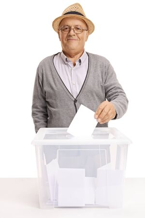 Elderly man putting a voting paper inside a box and looking at the camera isolated on white