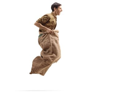Profile shot of a young man jumping with a sack isolated on white