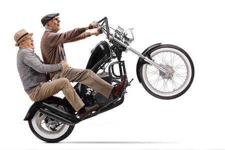 Crazy senior men riding a motorbike on one wheel isolated on white background