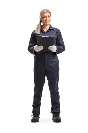 Full length portrait of a female worker in an overall uniform holding a clipboard isolated on white