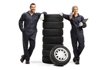Full length portrait of male and female auto mechanics with a pile of tires isolated on white background