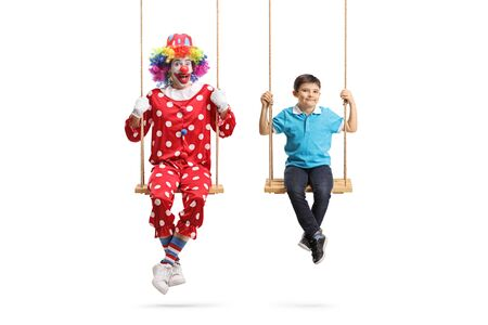 Clown and a boy swinging on swings isolated on white
