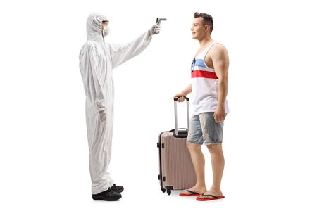 Full length profile shot of a man in a hazmat suit measuring temperature of a male tourist with a suitcase isolated on white background