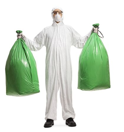 Full length portrait of a man in a decontamination suit holding plastic waste bags isolated on white background