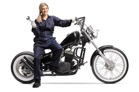 Female mechanic in a ubiform sitting on a motorbike isolated on white background
