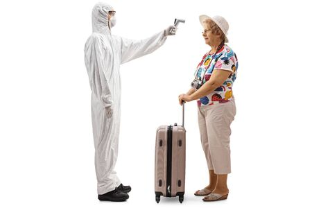 Full length profile shot of a man wearing a white protective suit and measuring temperature of an elderly woman with a suitcase isolated on white background 写真素材
