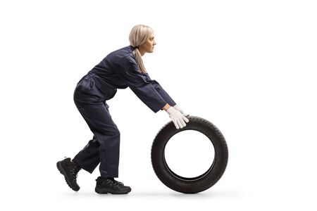 Full length profile shot of a female auto mechanic rolling a tire on the ground isolated on white background