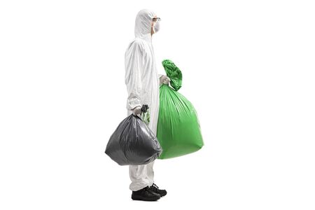 Full length profile shot of a man in a protective suit holding waste bags isolated on white background