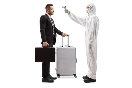 Full length profile shot of a man in a hazmat suit measuring body temperature with a thermometer to a businessman with a suitcase isolated on white background 写真素材